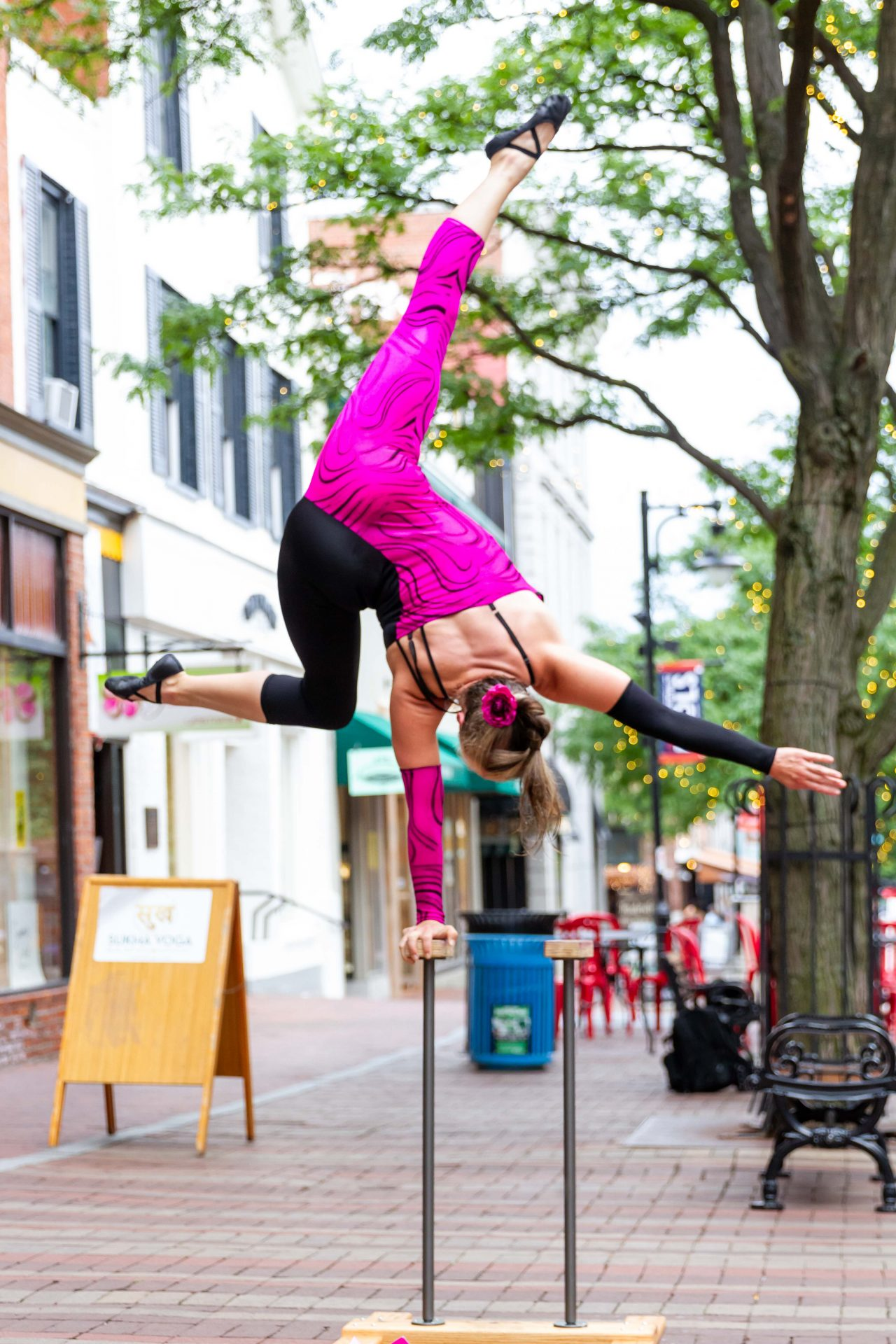 Megan Gendell in a one-arm handstand busking