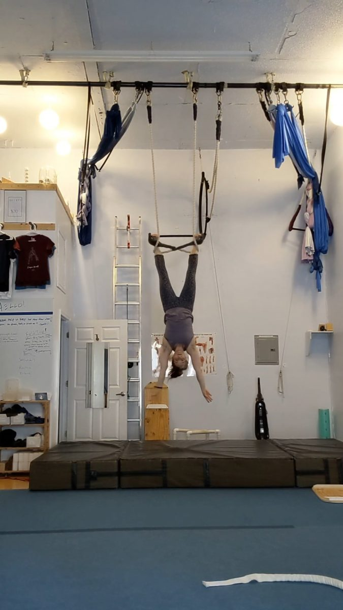 Megan hanging upside down from the trapeze in a move called cat's cradle
