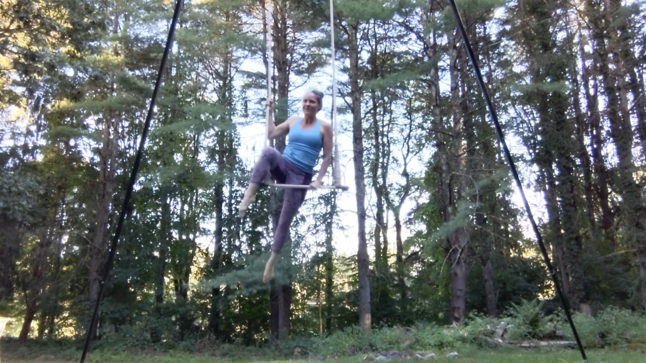 Megan with knee hooked on trapeze rope