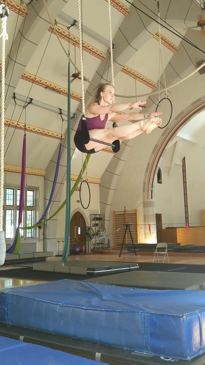 Megan balances in a pike sitting on the trapeze