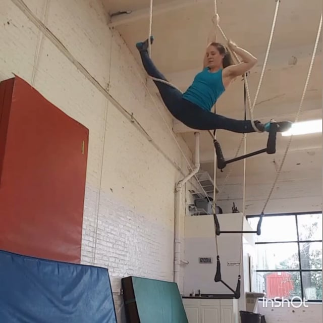 Megan in a straddle split on trapeze ropes