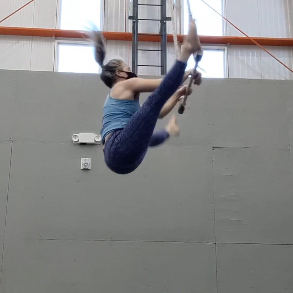 Megan in midair reaching for the trapeze