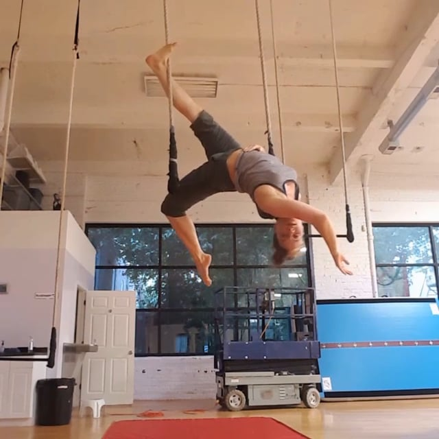 Megan arched in diagonal back balance on trapeze