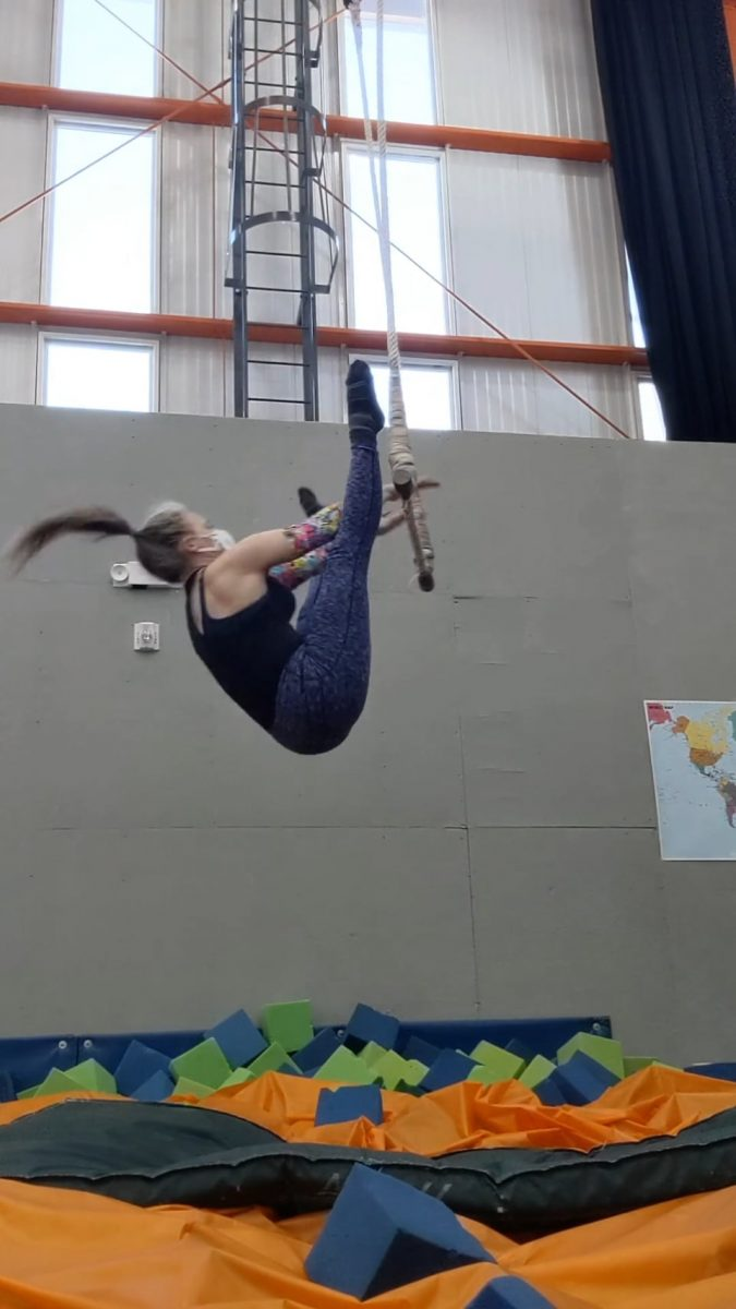 Megan reaches for the trapeze bar in a release move